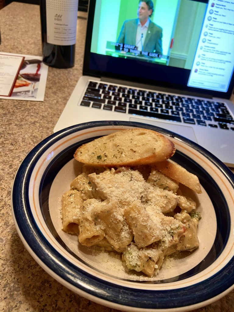 Pasta dinner and bottle of wine sitting in front of a laptop with the streaming event
