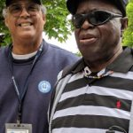 Junior, wearing a striped shirt and sunglasses and standing with Ray, who is smiling