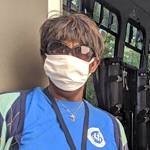 Woman wearing a face mask, sunglasses, and blue shirt with Medical Motor Service logo