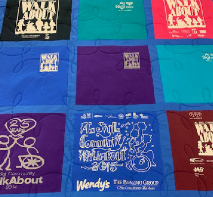 Quilt made of pink, teal, blue, purple and black t-shirts.